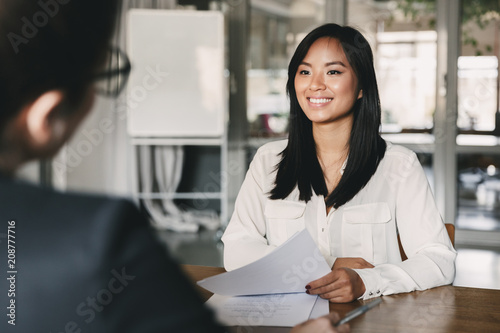 Photo  Portrait of joyful asian woman smiling and holding resume, while sitting in fron
