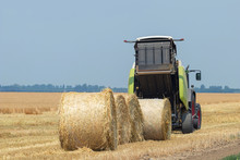 Tractor And Round Baler Discharges. Straw Bales.