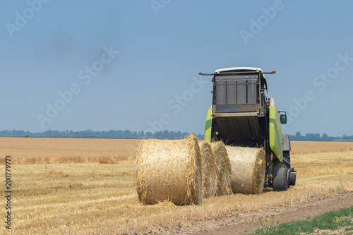 Photo Tractor and round baler discharges. Straw Bales.