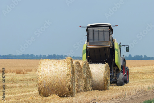 Tractor and round baler discharges. Straw Bales. Canvas Print