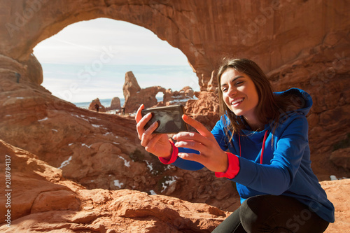 Female traveller taikng self portraits with rock formation in the Arches Nationa Fototapete
