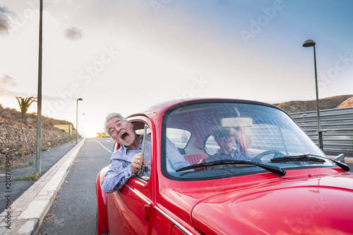 Fotografía  nice beautiful senior adult couple traveling together while the woman drive and the man shout for scare or for craziness
