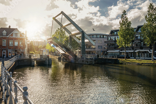 Tree-lined wide canal with houses and lifted bascule bridge on sunset in Weesp Wallpaper Mural