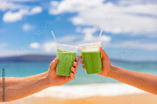 Couple toasting healthy juice drinks together at beach restaurant. Detox smoothie drink toast at summer vacations holidays. Fruit juicing weight loss diet.