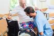 canvas print picture - Altenpfleger hilft älterem Mann aus Rollstuhl ins Bett