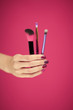 Leinwanddruck Bild - womans hand with perfect pink nail polish holding cosmetic brushes in front of pink background