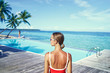 Summer vacation and fashion. Young woman in red swimsuit enjoying the view near swimming pool on tropical beach.
