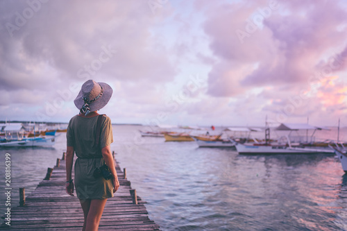 Foto auf AluDibond Flieder Photography and travel. Young woman in hat holding camera standing on wooden fishing pier with beautiful tropical sea view.