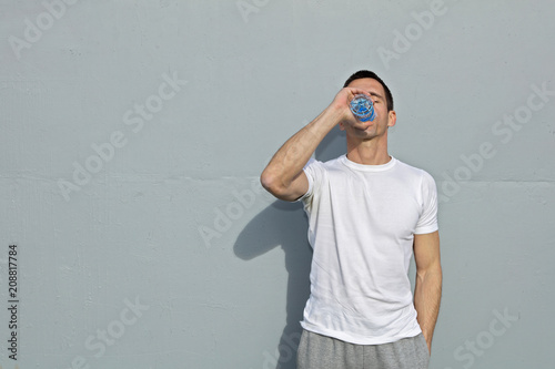 Man runner drinking water after workout outdoors Canvas Print