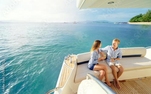 Garden Poster Water Motor sports Romantic vacation and luxury travel. Young loving couple sitting on the sofa on the modern yacht deck. Sailing the sea.