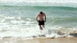 Young man getting out of the sea, slow motion shot at 240fps
