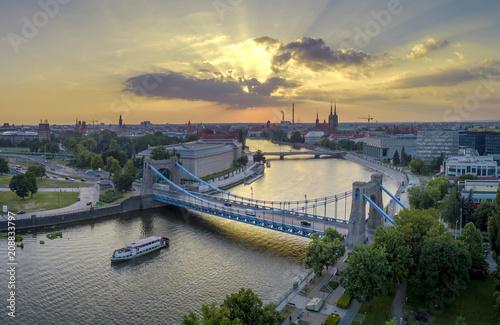 Widok z lotu ptaka na mosty, statek na rzece oraz zachodzące słońce - Wrocław, Polska