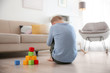 canvas print picture - Lonely little boy with cubes sitting on floor at home. Autism concept