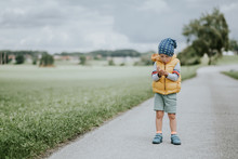 Little Boy Standing Looking At His Hands