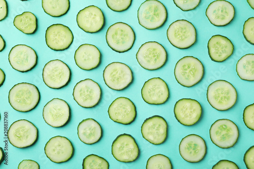 Flat lay composition with slices of cucumber on color background