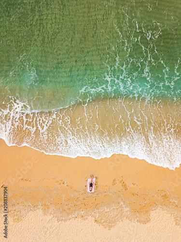 Staande foto Strand Woman sunbathing alone on an empty beach