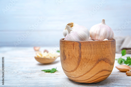 Acrylic Prints Bird-of-paradise flower Wooden bowl with fresh garlic bulbs on table