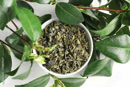 Carta da parati Cup with dry tea and fresh plant on table, top view