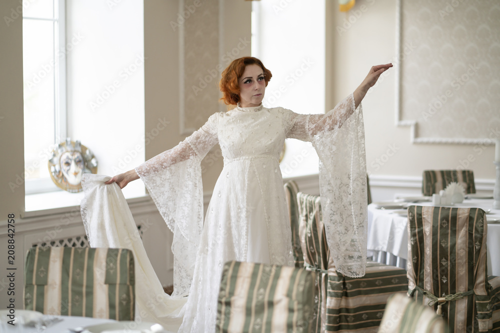 Fototapeta a dying seriously ill woman in a white dress waiting for Breakfast in an empty restaurant alone