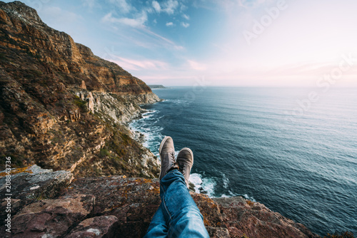 Point of views of crossed legs and shoes with a scenic view mountains, coast and sea at sunset