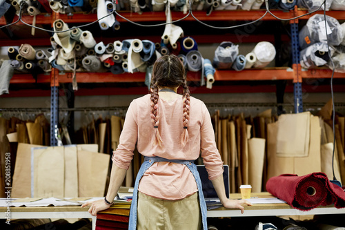Female Worker Looking At Fabrics And Cardboard At Sofa Workshop