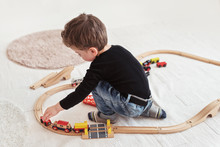 Child Playing With Wooden Toy Trains On The Floor Indoors