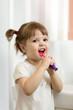 Cute toddler girl brushing teeth in bathroom