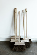 Small Wooden Brooms Leaning Against White Wall In Curated Shop