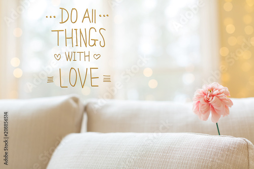 Photo  Do All Things with Love message with a flower in a bright interior room sofa
