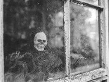 A Ghoulish Figure At An Old Wi...