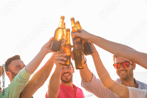 Fotografía  Cheers! Group of happy young people are toasting with bottles of beer in the beach