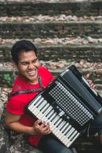 Asian Man Playing An Accordion...
