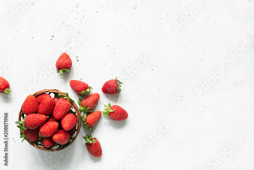 Fresh strawberry in bowl on bright gray concrete background. Strawberries in a bowl. Top view of fresh juicy strawberries