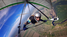 Brave Hang Glider Pilot Soar High Over Town And River.