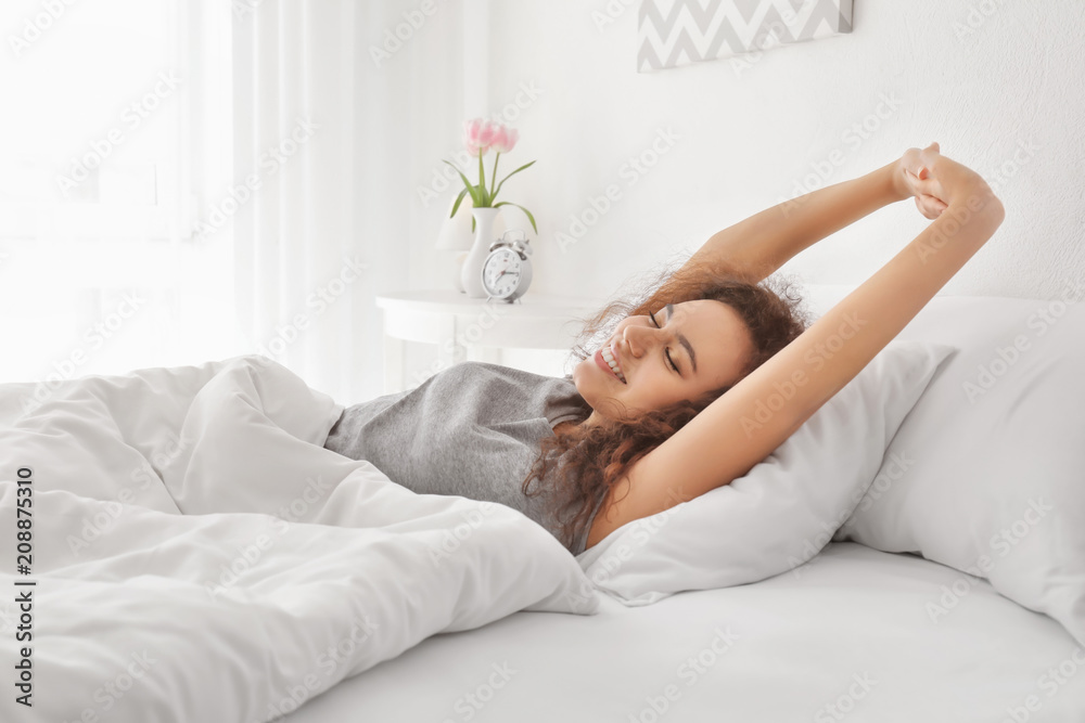 Fototapeta Morning of young African-American woman in bed