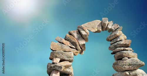 Stampa su Tela stone cairn forming arc on sunny blue sky