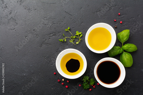 Soy sauce, olive oil and balsamic sauce with herbs basil, parsley, pepper and thyme in white ceramic bowls on black stone or concrete background.