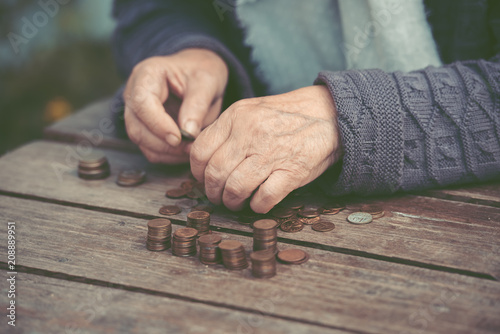 Fototapety, obrazy: Money, coins, the grandmother on pension and the concept of life, minimum - wrinkled hands of the old woman touch coins on a wooden table