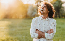 Handsome Happy Young Male Smiling With Curly Hair Posing In The City Park Looking At The Sky, Cross His Hands And Dreaming. Copy Space For Your Advertising. People, Lifestyle And Emotion Concept