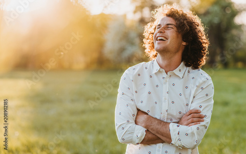 Leinwand Poster Handsome happy young male smiling with curly hair posing in the city park looking at the sky, cross his hands and dreaming