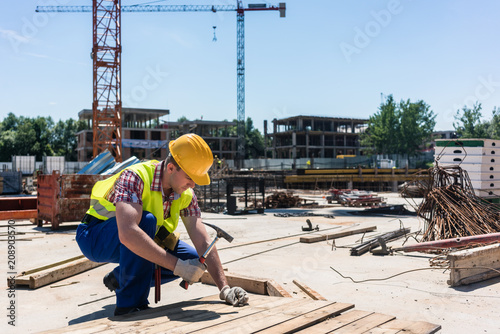Fototapeta Side view of a young worker wearing safety vest and yellow hard hat, while hamme
