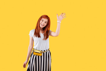 Hey you. Cheerful delighted woman waving her hand while greeting you
