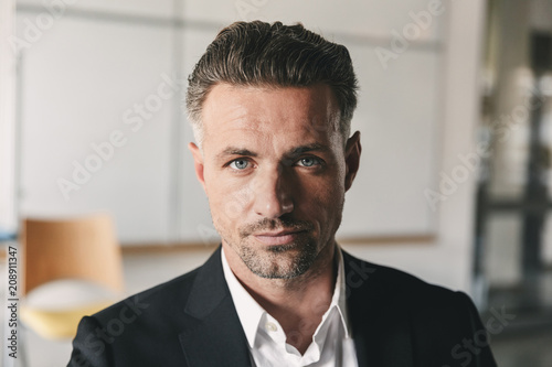 Portrait closeup of serious concentrated businessman wearing white shirt and black suit looking at camera, while working in office room