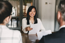 Business, Career And Recruitment Concept - Young Asian Woman Smiling And Holding Resume, While Interviewing As Candidate For Job In Big Company