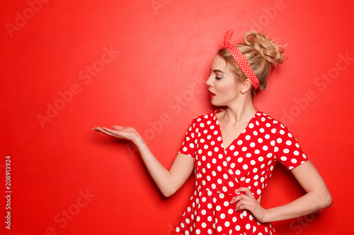 Fotografie, Obraz  Portrait of beautiful young woman holding something on color background