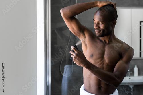 Photo smiling african american man in towel holding deodorant spray in bathroom