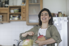 Smiling Woman Standing In The Kitchen Using An Old Coffee Mill