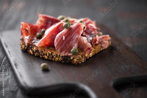 Fotografía Traditional Spanish Jamon Serrano ham, Prosciutto Crudo, Parma ham, Italian antipasto, served on toasted bread