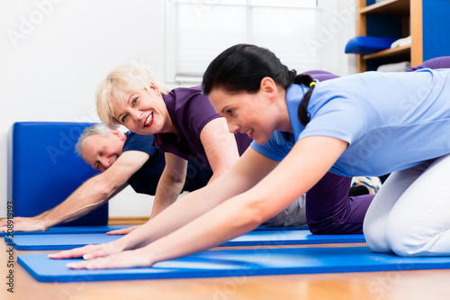Senior woman and man doing floor gymnastics with physiotherapist