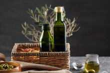Wicker Basket With Bottles Of Olive Oil On Table